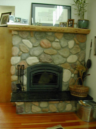 Granite hearth and ponderosa pine stone fireplace by Bragg Construction