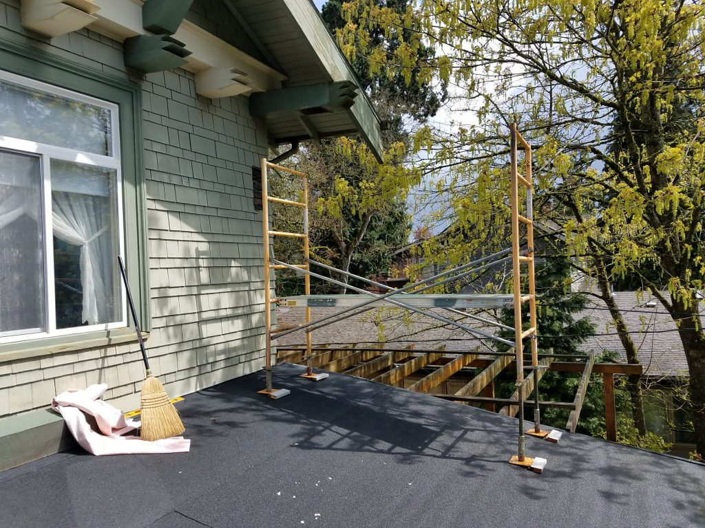 Scaffolding set up with adjustable feet on sloped porch roof