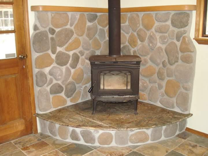 Stone and granite fireplace with fir mantle custom build by Bragg Construction and Remodeling